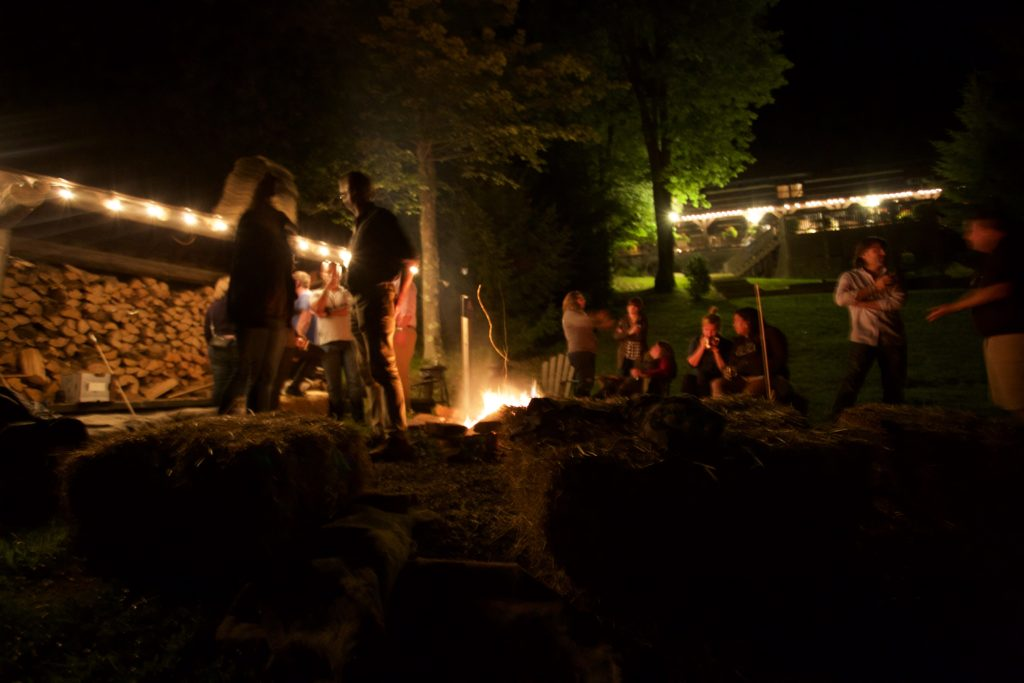 The Cultivate the Karass cohort stands and sits around a fire at night.