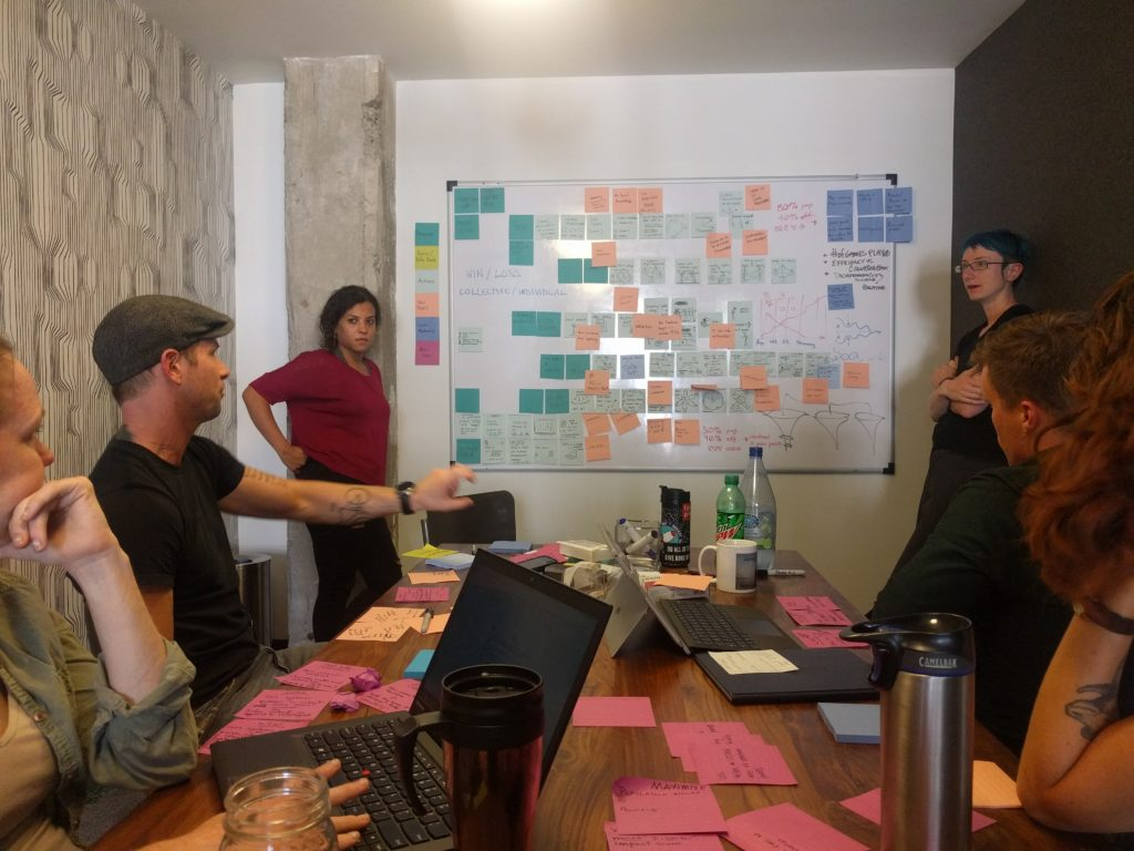 Participants broke down workflows into one component per sticky note, laid out in linear fashion. Wafaa and Willow stand at the board while others talk through potential overlaps.