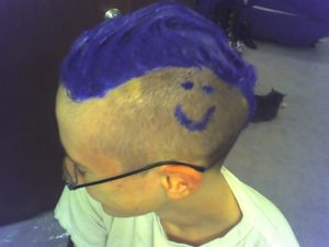blue dye is now applied throughout the mohawk. in addition, a smiley face is drawn on the short hair on the side of the head