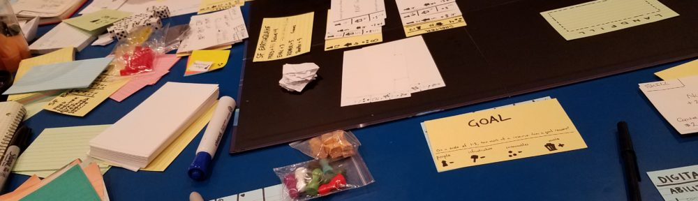 Cards scatter the tabletop in a variety of colors, and with drawings on them.
